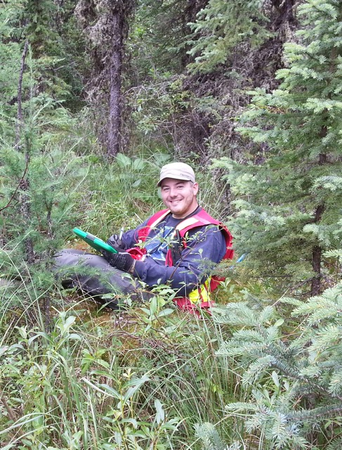 ACER alumnus Jason Weiler holding a clipboard and smiling while working in the forest, surrounded by trees and greenery.