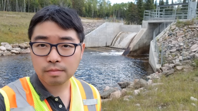 ACER Alumni Daniel Kim stands in front of a watercourse in 2019.