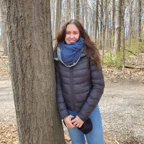 ACER Alumna Julia Bilas stands smiling next to a tree in the woods.