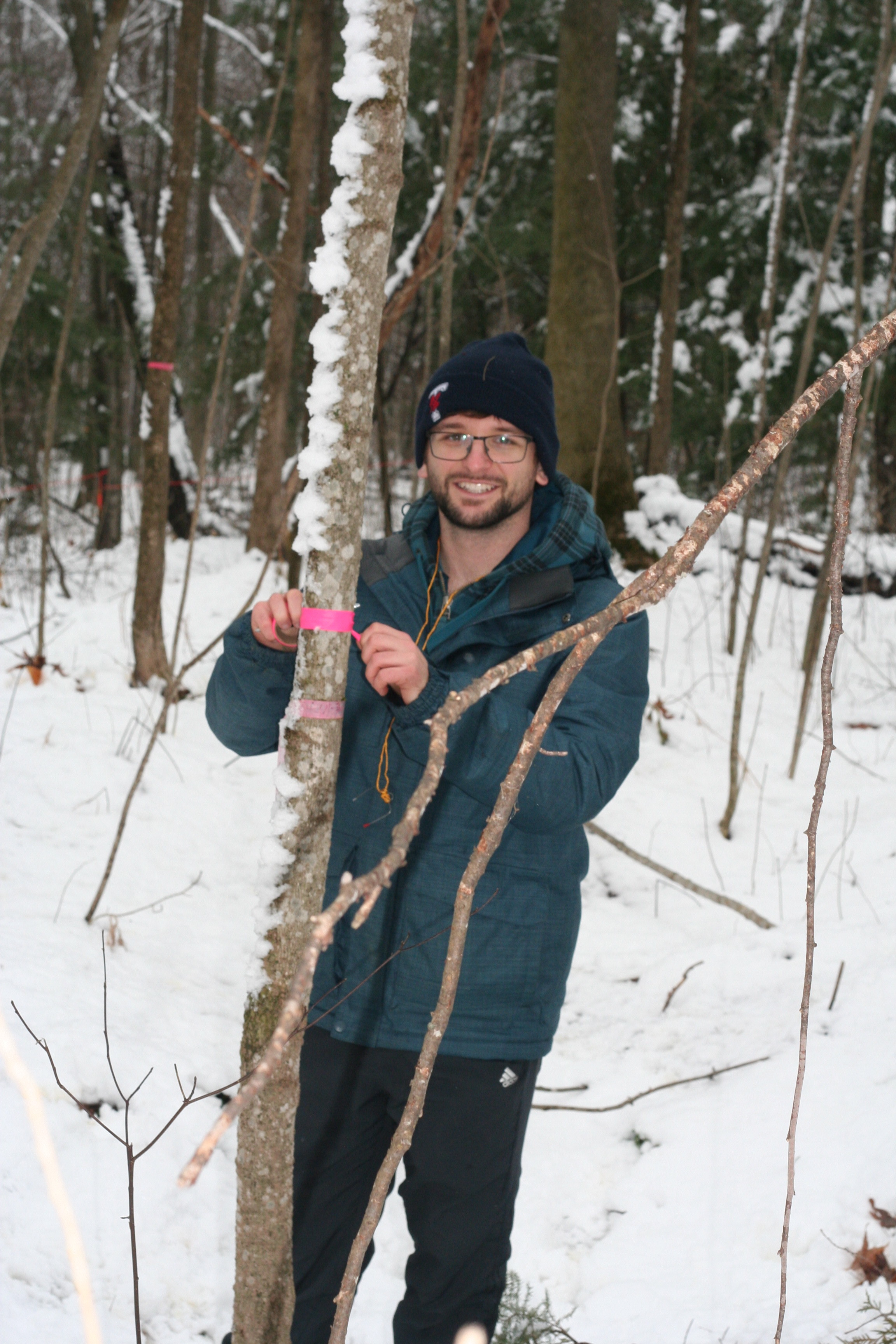 ACER Alumnus Tyler Orsulak during his 2019 internship, measuring a tree in the snow.