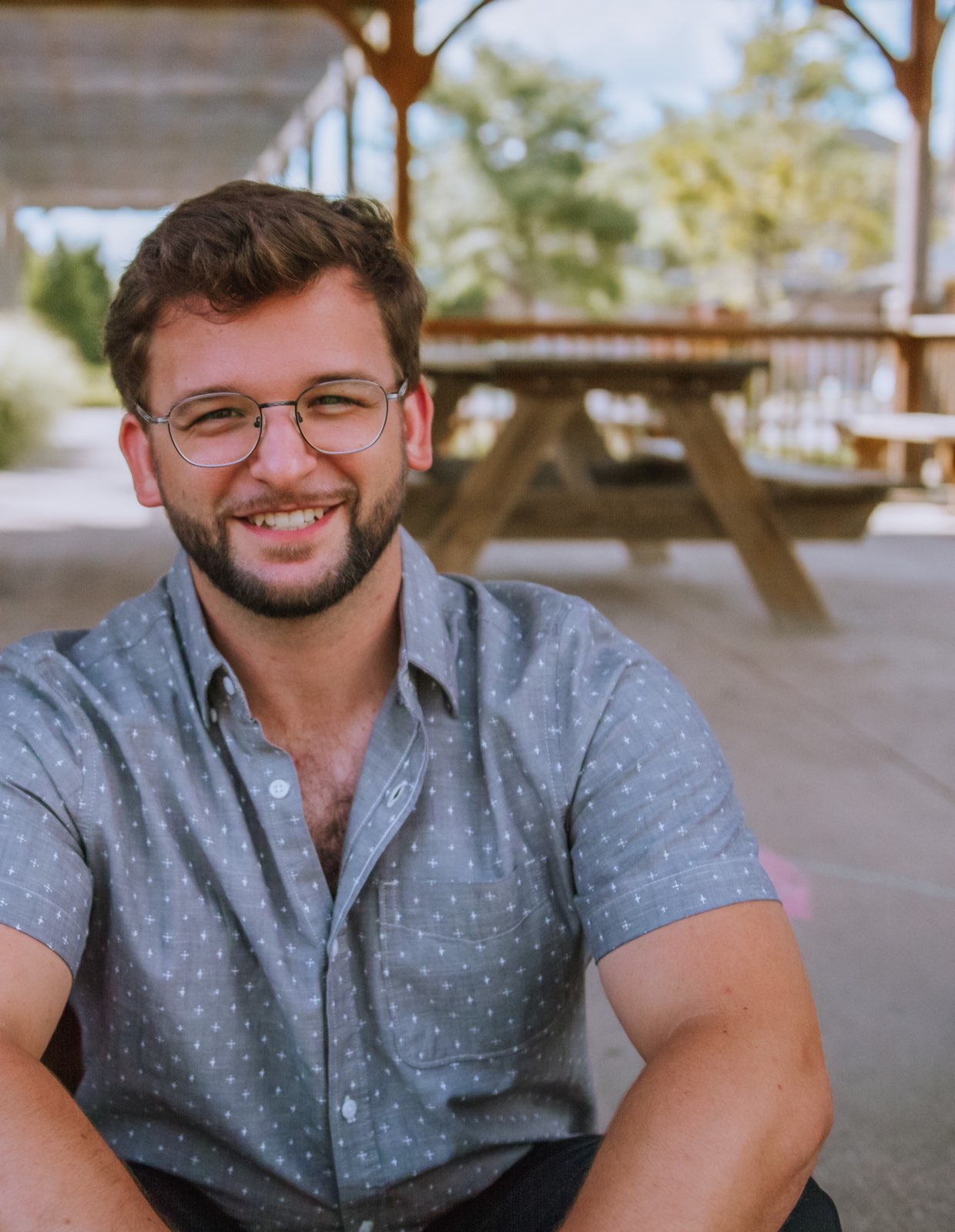 ACER Alumnus Tyler Orsulak sits smiling in front of a picnic table.